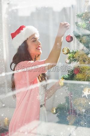 composite image of festive brunette decorating