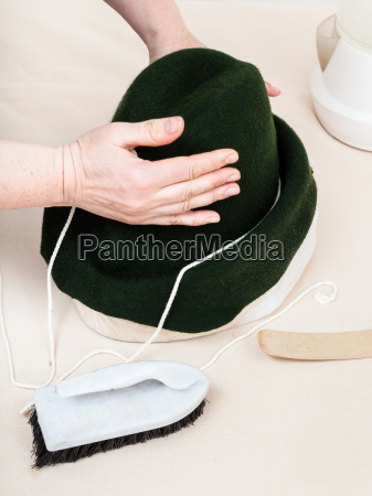 hatter fixes a felt hood on