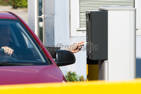 man inserting ticket for parking area