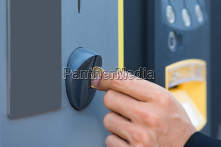 persons hand inserting coin at parking