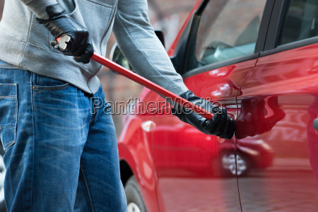 thief opening cars door with crowbar