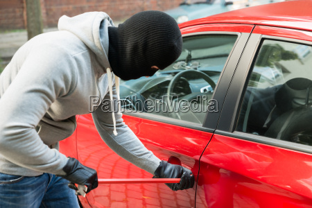 thief with mask using crowbar to