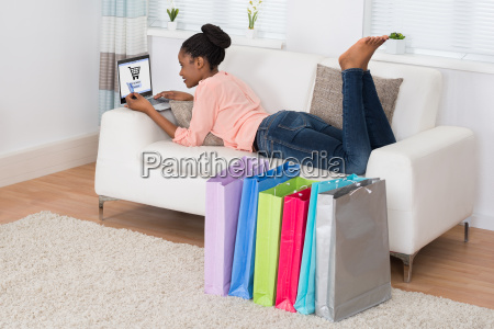 young woman lying on sofa shopping