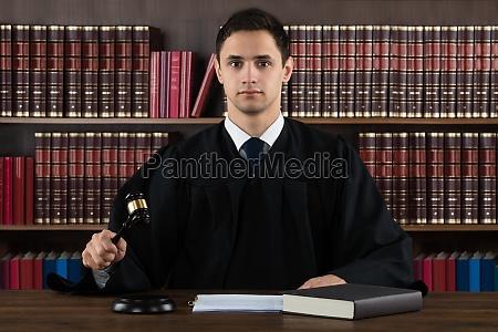 retrato de juez confiado golpeando mazo