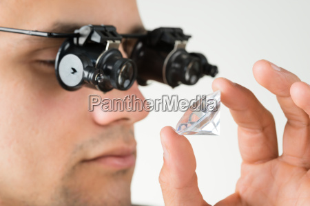 jeweler examining diamond with magnifying glass