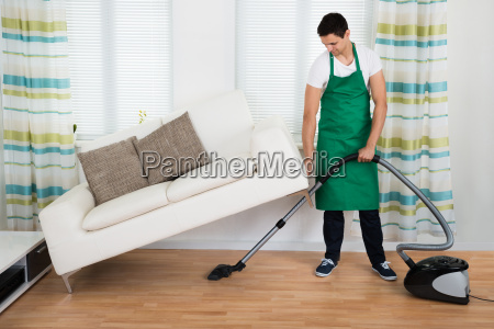 man lifting couch while cleaning floor