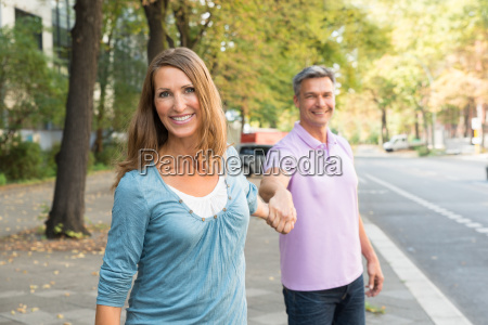 man pulling woman in the street