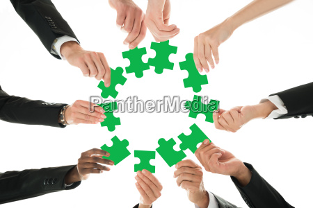 business team joining jigsaw pieces in