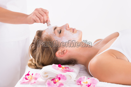 beautician applying mask on customers face
