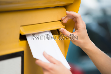 womans hands inserting letter in mailbox
