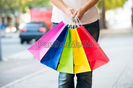 midsection of woman holding colorful shopping