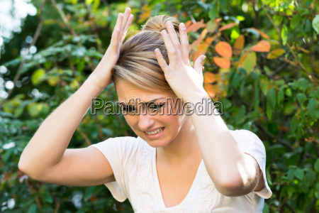 woman with hands on head against