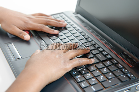 black woman hands on laptop keyboard
