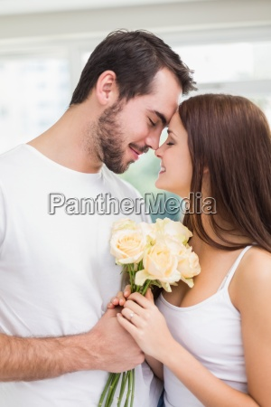 young man giving girlfriend white roses