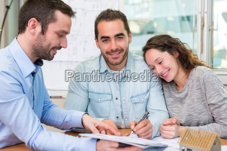 young attractive people signing cotract with