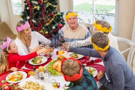 family in party hat toasting at