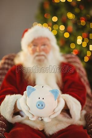 santa claus offering piggy bank