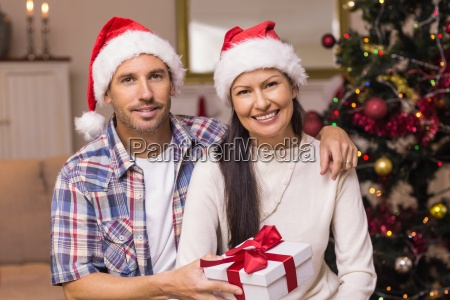 smiling couple in santa hat holding