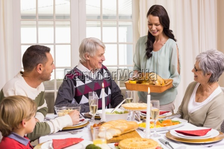 woman holding turkey roast with family