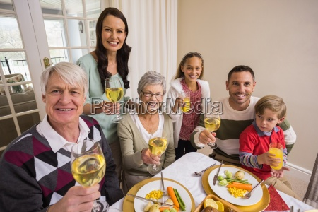 smiling family toasting to camera during