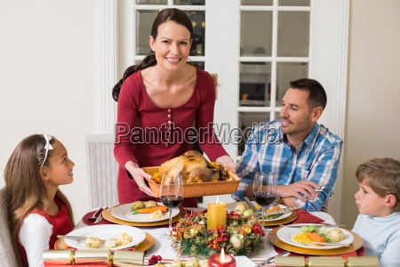 smiling woman serving roast turkey to