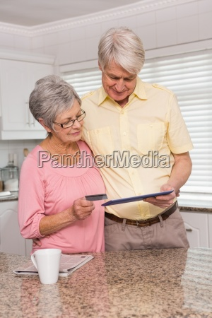 senior couple shopping online with tablet