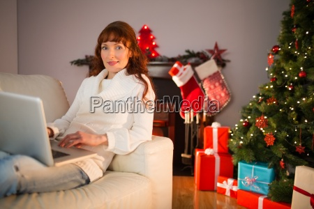 smiling redhead woman using laptop on