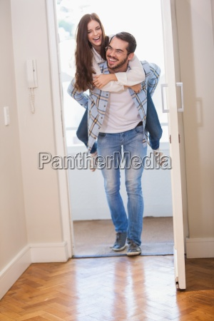 young man giving girlfriend a piggyback