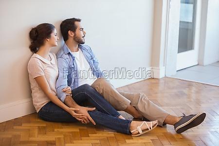 cute couple sitting on floor against