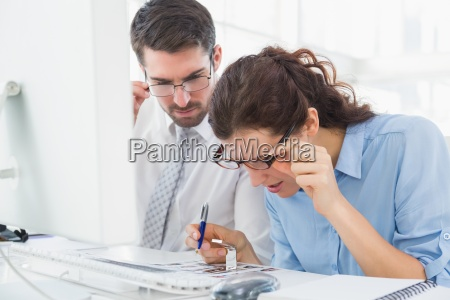 focused coworkers looking photos together