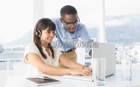 smiling coworkers using laptop and headset