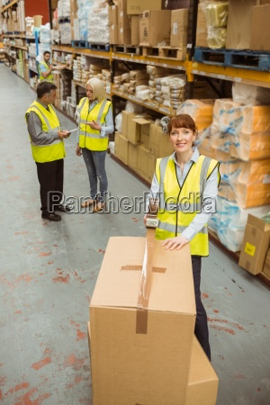 warehouse worker sealing cardboard boxes for