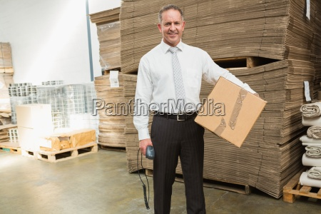 warehouse manager holding cardboard box and