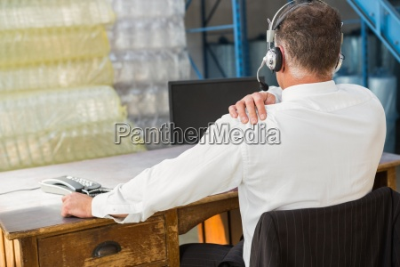rear view of warehouse manager using