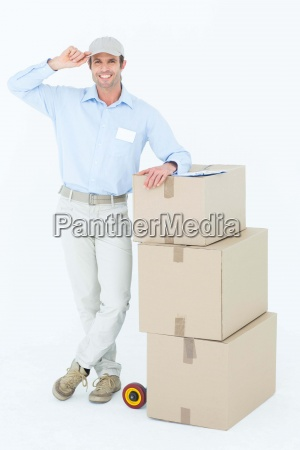 happy delivery man leaning on stacked