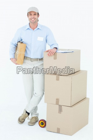handsome delivery man leaning on stacked