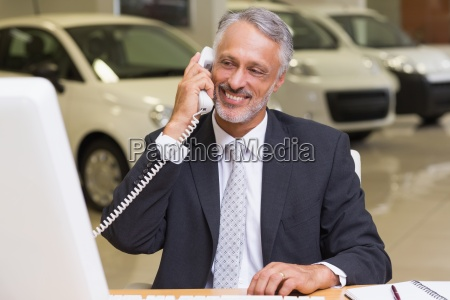 smiling businessman using phone in front