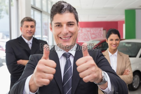 smiling business team standing while one