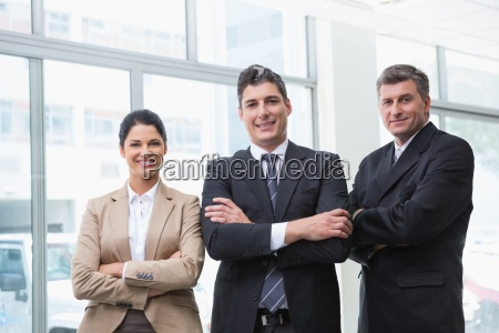 smiling business team standing with arms