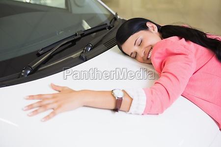 smiling woman hugging a white car