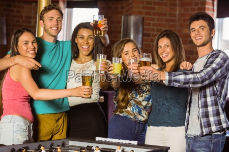 portrait of happy friends toasting with