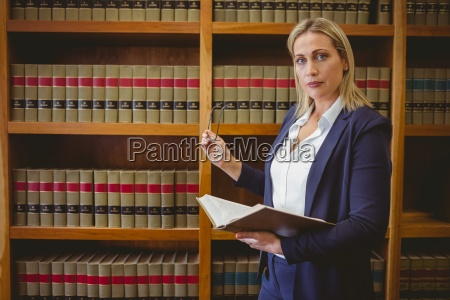 focused librarian holding book and reading