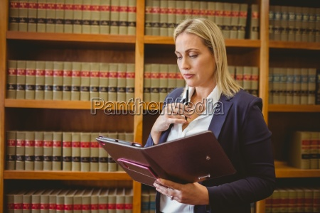 thinking female librarian holding textbook