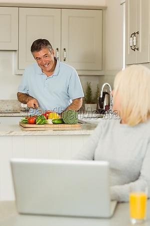 happy mature blonde using laptop talking