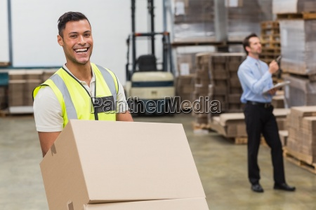 smiling warehouse worker moving boxes on