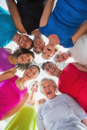 cheerful people forming huddle at gym