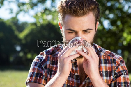 handsome hipster blowing his nose