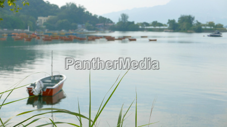 red fishing boat on peaceful lake