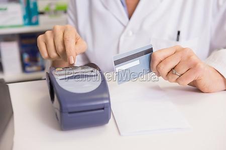 pharmacist using keypad and holding credit