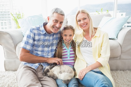 happy parents and daughter with rabbit